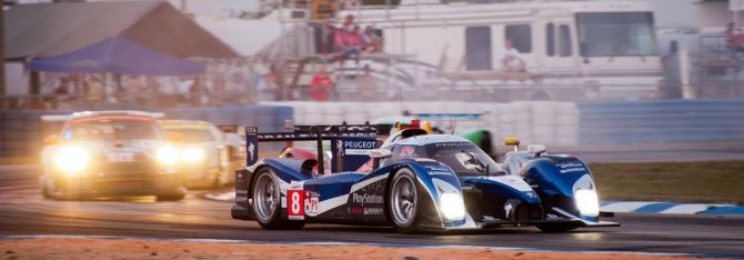 Peugeot number 8 leads traffic through turn 5 at dusk